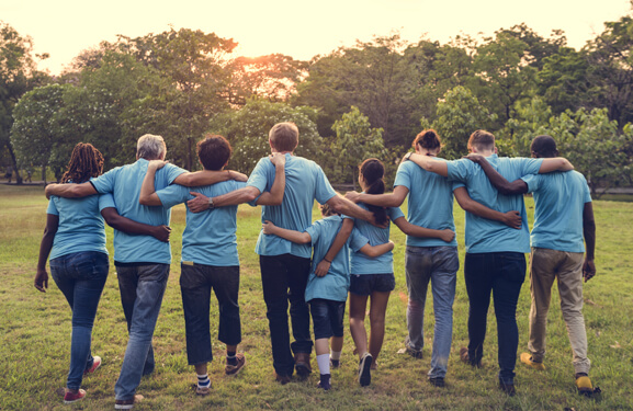A diverse group of people wearing blue T-shirts walk with their arms around each other away from the observer in the direction of a wood at dusk.