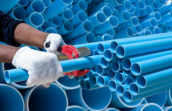 Stacked blue plastic tubes with the hands of a worker in the foreground who is cutting one of the tubes using pliers