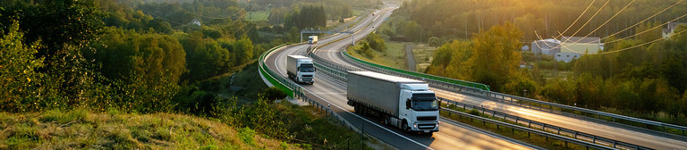 Two lorries driving on a motorway surrounded by green forests at dusk.