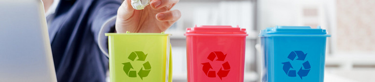 Three mini-waste bins in green, red and blue and featuring the recycling symbol standing on an office desk. Behind them, a smiling woman can be seen working at a laptop, who is throwing a crumpled piece of paper into the green bin.