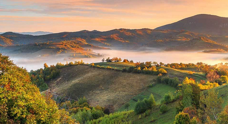 Romanian natural landscape with meadows, forests and misty mountains at dusk